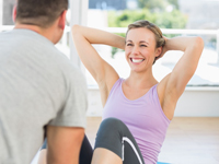 Trainer assisting fit woman in doing sits up
