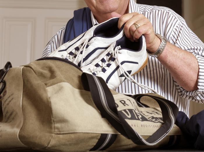 Älterer Herr packt Sporttasche